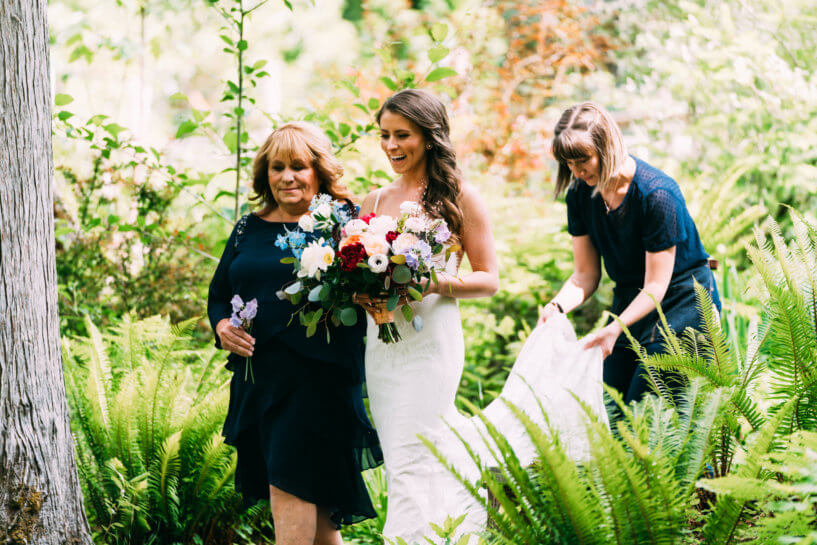 wedding planner helping bride down aisle