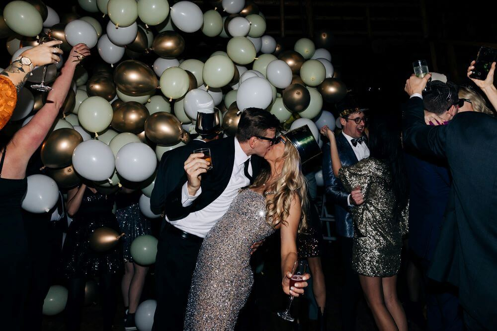 bride and groom kissing during balloon drop